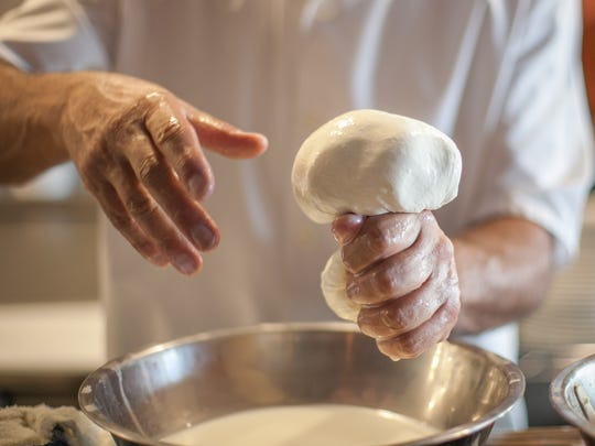 Bill Forrest pinches off a ball of mozzarella cheese