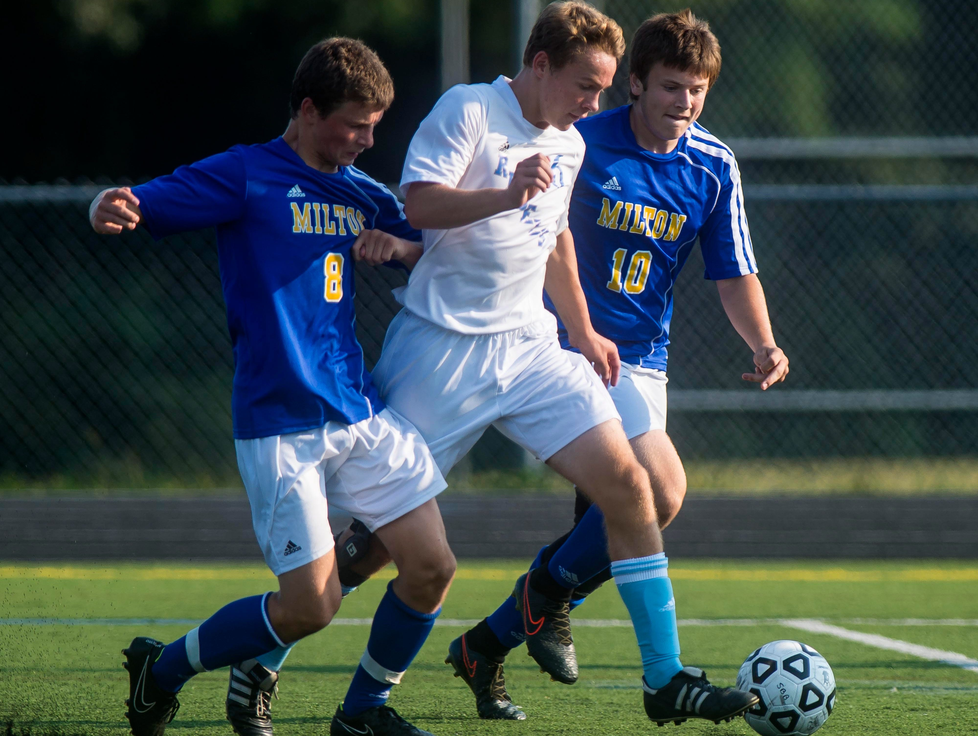 South Burlington's Patrick O'Hara, center, is pressured by Milton's Cam Goodrich, left, and Ryan Collette in South Burlington on Tuesday, September1, 2015.