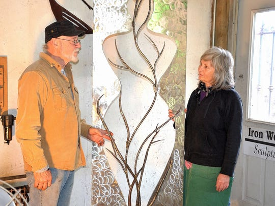 """Dan and Tekla Howachyn stand on either side of Tekla's """"Tree of Life"""" sculpture."""