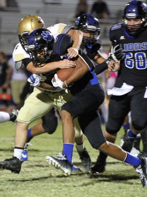 Cathedral City's Jordan Wallace tries to break the tackle of Xavier Prep's Nick Mezacapa during the first half of the game in Cathedral City on Friday, October 2, 2015.