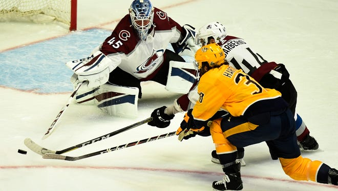 Predators right wing Ryan Hartman (38) and Avalanche defenseman Mark Barberio (44) try to move the puck in front of Avalanche goalie Jonathan Bernier (45) during the second period in game 2 of the first round NHL Stanley Cup Playoffs at Bridgestone Arena Saturday, April 14, 2018, in Nashville, Tenn.