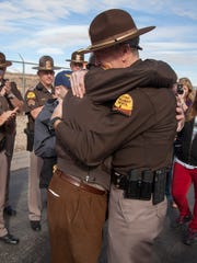 Members of the Utah Highway Patrol place a cross along I-15 in memorial of Trooper Eric Ellsworth Friday, Dec. 30, 2016. Ellsworth died in November after being struck by a vehicle while on duty.