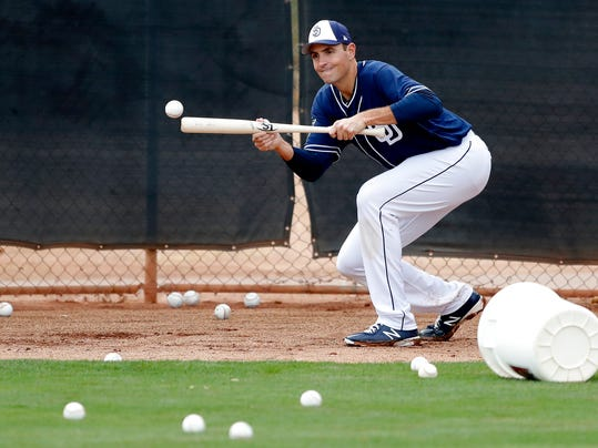 """File-This photo taken Feb. 16, 2018, shows San Diego Padres pitcher Chris Young bunting during a baseball spring training workout in Peoria, Ariz. Young is back with the Padres and trying to earn a spot on the staff, whether it's in the rotation or in the bullpen. """"Archaic, maybe, but I don't know about historic,"""" the 38-year-old said with a laugh. Actually, he is historic. Young is the last Padres pitcher to win a playoff game.  (AP Photo/Charlie Neibergall, File)"""