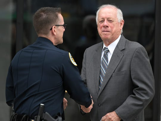 Former Gov. Phil Bredesen shakes hands with a Nashville police officer after the memorial service for Max Barry, son of Mayor Megan Barry, at the Belcourt Theatre in Nashville