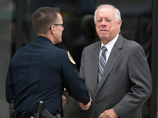 Former Gov. Phil Bredesen shakes hands with a Nashville police officer after the memorial service for Max Barry, son of Mayor Megan Barry, at the Belcourt Theatre in Nashville, Tenn. Tuesday, Aug. 1, 2017.