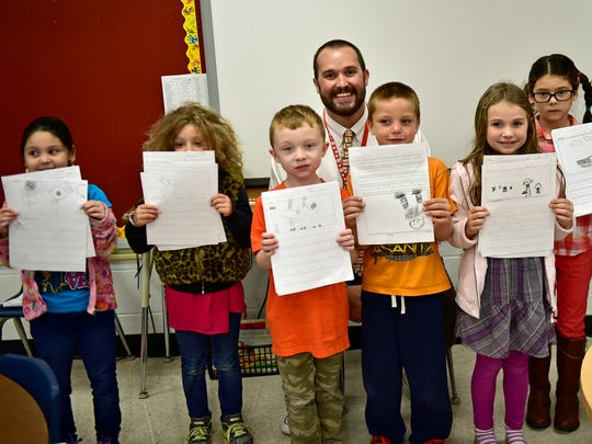 Students pose with Drew Kyle during the Principal's Publishing Party on Thursday, Oct. 6, 2016 at St. Thomas Elementary School.