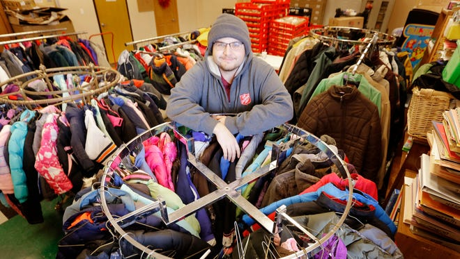 Salvation Army seasonal operations employee Chris Abbott stands next to some of the coats that have been collected for the Coats for Kids drive, in Sioux City, Iowa.