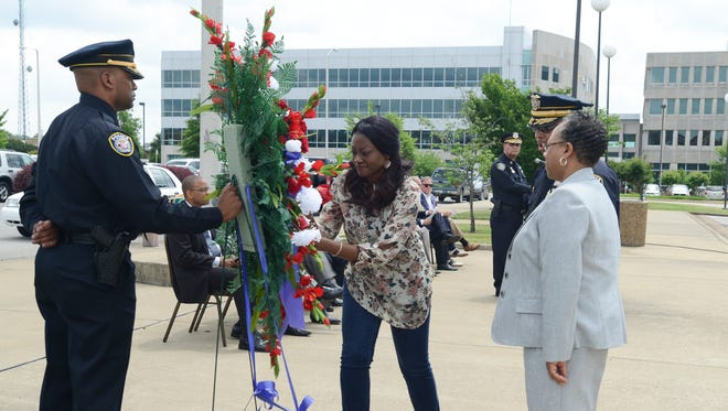 Brooke Bailey places a flower on a wreath Friday afternoon during the National Police Memorial Day ceremony at the Carl Perkins Civic Center to honor her father, Sgt. Andy Bailey, who was killed in the line of duty.