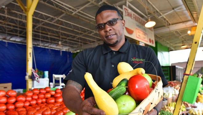 Chef Nick Wallace. executive chef at the Mississippi Museum of Art, gathers fresh produce at Doris Berry's Old Farmer Market Stand near Woodrow Wilson Avenue in Jackson.