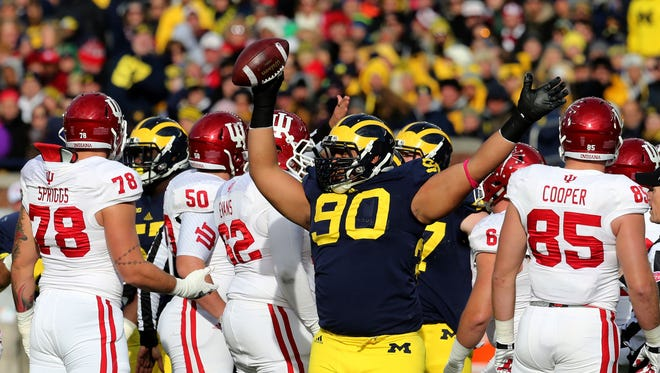 Michigan's Bryan Mone (90) recovers a fumble during first-quarter action against Indiana at Michigan Stadium in Ann Arbor, Mich., on Saturday, Nov. 1, 2014.