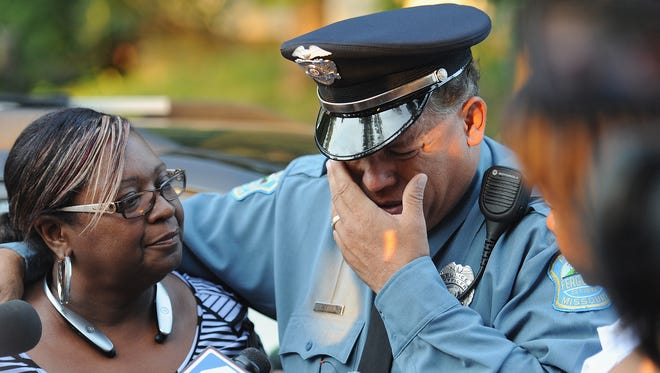A Ferguson, Mo., police officer is overcome with emotion during a candlelight vigil Aug. 20, 2014, in honor of Jamyla Bolden, 9,  who was struck by a stray bullet from a drive-by shooting and killed while doing her homework.