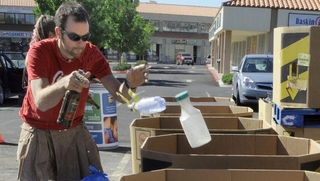 Andrew Campbell of San Francisco,  takes advantage of recycle bins Monday set up at Save-Mart at Fifth Street and Keystone Avenue after a past Burning Man.