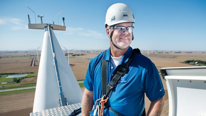 Bill Nosbisch, manager of engineering and asset management at MidAmerican Renewables, smiles as he stands Thursday on top of a Siemens wind turbine during a media event at Highland Wind Farm at O'Brien County near Primghar.