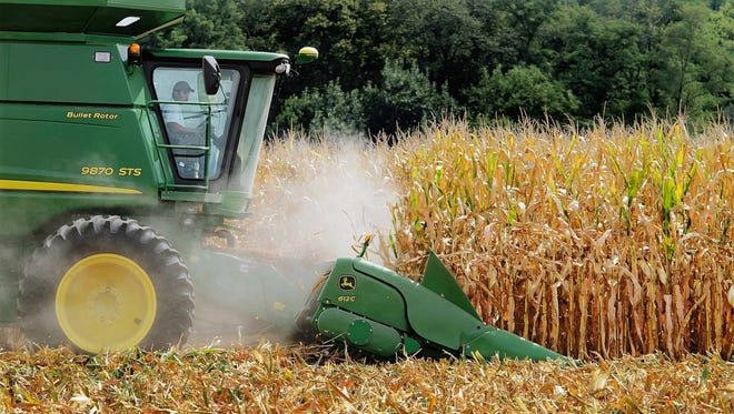 This Aug. 30, 2011 file photo, farmer Jason Podany uses combine to harvest corn near Farmingdale, Ill.