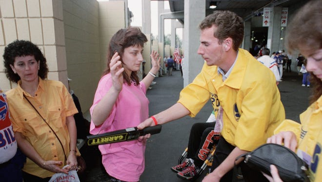 A security guard uses a metal detector on fans as they enter Tampa Stadium for Super Bowl XXV.