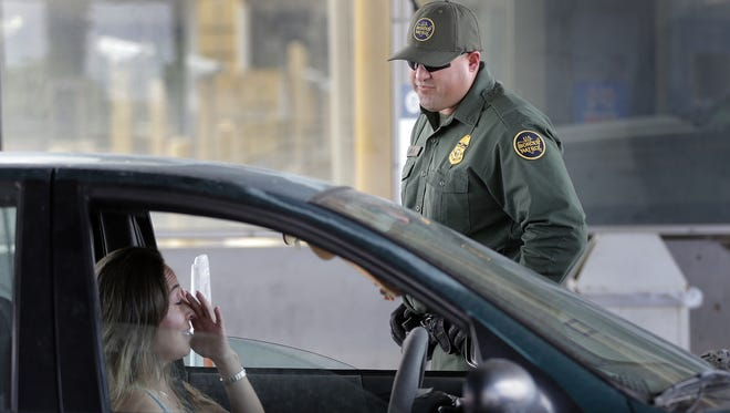U.S. Border Patrol Agent Anthony Garcia keeps a lookout for stolen vehicles Friday at the outbound inspection area of the Bridge of the Americas. While the Border Patrol's primary mission is not stolen vehicles, agents do find them from time to time.