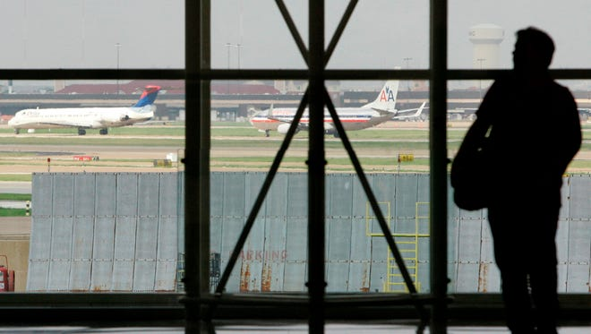 A traveler is seen in Terminal C at Dallas Fort Worth International Airport as aircraft, rear, taxi along a runway in Grapevine, Texas.