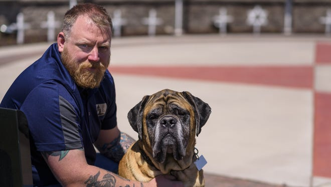 Kaukauna's Tony Austin helped start a nonprofit in October 2015 to work one-on-one with veterans in need of service dogs. Austin is pictured here with his service dog, Hadji, at the Veteran's Memorial Ring of Honor in Kaukauna.