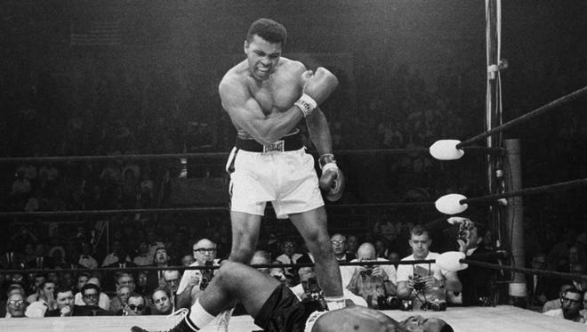 Heavyweight champion Muhammad Ali stands over fallen challenger Sonny Liston on May 25, 1965, in Lewiston, Maine. The bout lasted only one minute into the first round.