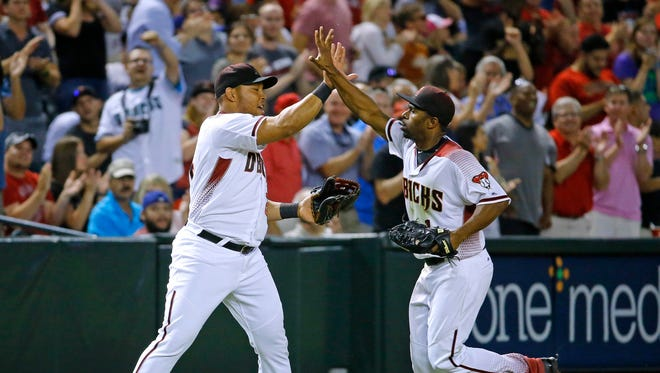 Arizona Diamondbacks left fielder Yasmany Tomas (24) greets center fielder Michael Bourn (1) after a diving catch with bases loaded to end the 8th inning of their MLB game Monday, June 13, 2016 in Phoenix,  Ariz.