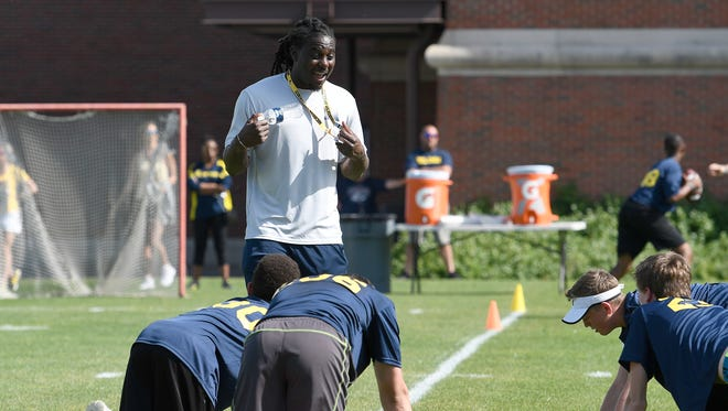 Former Michigan quarterback Denard Robinson has campers do pushups for not listening well enough during drills Saturday.