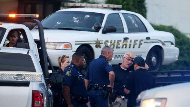 BATON ROUGE, LA - JULY 17:  Police officers stand in front of an East Baton Rouge police car with bullet holes as it's towed away from the scene where three police officers were killed this morning on July 17, 2016 in Baton Rouge, Louisiana. The suspect, identified as Gavin Long of Kansas City, is dead after killing three police officers and injuring three more. (Photo by Sean Gardner/Getty Images)