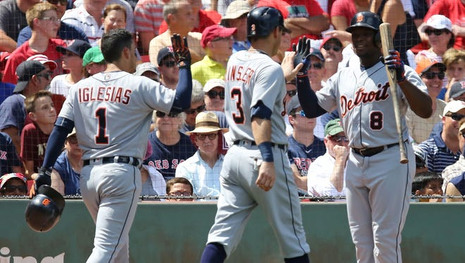 Jose Iglesias #1 and Ian Kinsler #3 high five Justin Upton #8 of the Detroit Tigers after scoring in the third inning during the game against the Boston Red Sox at Fenway Park on July 27, 2016 in Boston, Massachusetts.
