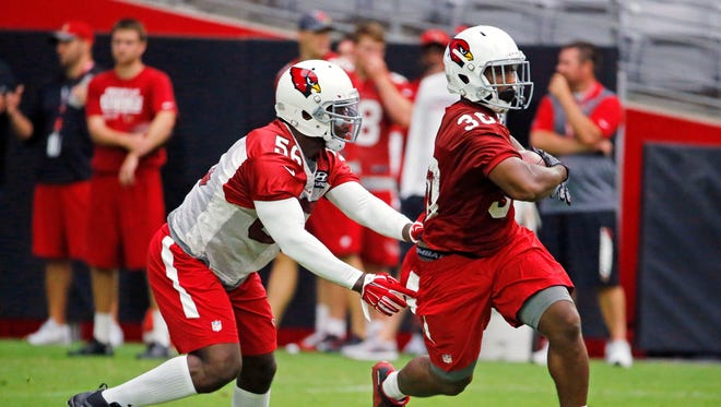 Arizona Cardinals running back Stepfan Taylor (30) gets away from linebacker Donald Butler (56) during training camp Saturday, July 30, 2016 in  Glendale, Ariz.