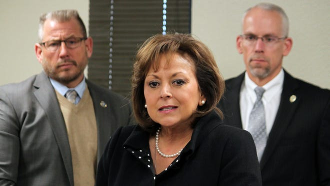 This Tuesday, Jan. 5, 2016 photo, Gov. Susana Martinez, center, unveils her budget priorities for the upcoming legislative session as Corrections Secretary Greg Marcantel, left, and Public Safety Secretary Greg Fouratt stand behind her during a news conference in Albuquerque, N.M. New Mexico officials are revising revenue expectations downward as state lawmakers confront state budget shortfalls reminiscent of the 2008 recession. Members of the Legislative Finance Committee that drafts the state budget are meeting Wednesday, Aug. 24, 2016, in the town of Red River. Martinez says she plans to reconvene lawmakers and has recommended all state agencies reduce spending by 5 percent.