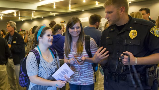 Bethany Busch and Ariel Kumbaler talk to Lt. Chris Tarmann of the UW-Oshkosh Police Department about safety on campus during the Take Back the Night rally Oct. 9, 2013.