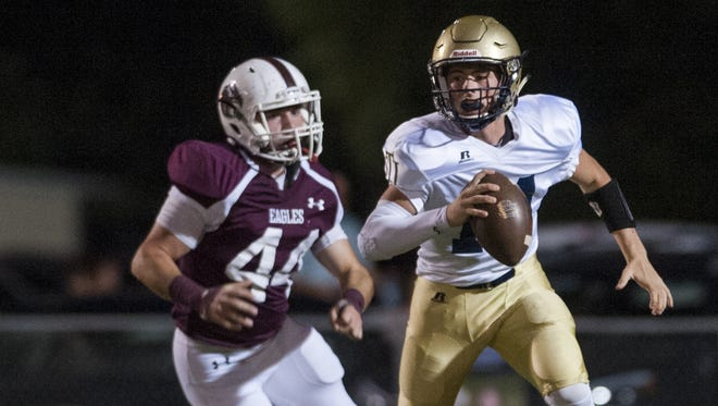 St. James' quarterback Joshua Garnett (14) is chased by Alabama Christian's John Marc Meyer (44) at the ACA campus in Montgomery, Ala., on Friday October 6, 2016.