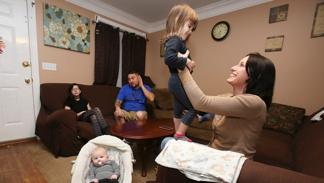 Amy Kalber, right, plays with her daughter, Rori Barkley (2) next to her most recent child Marty Barkley (3 months) at their home.  Kalber's first two children were born drug dependent, but her last two, Rori and Marty were born healthy during her recovery.   Nov. 28, 2016