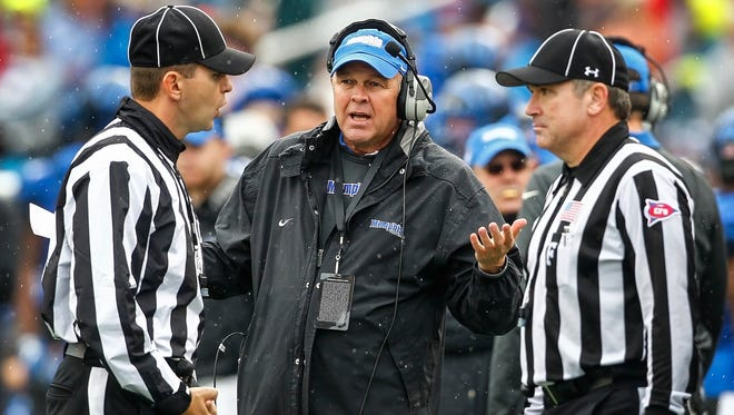 Memphis interim head coach Darrell Dickey (middle) chats with game officials during third quarter action against Auburn in the Birmingham Bowl at Legion Field in Birmingham, Ala., on Dec. 30, 2015.