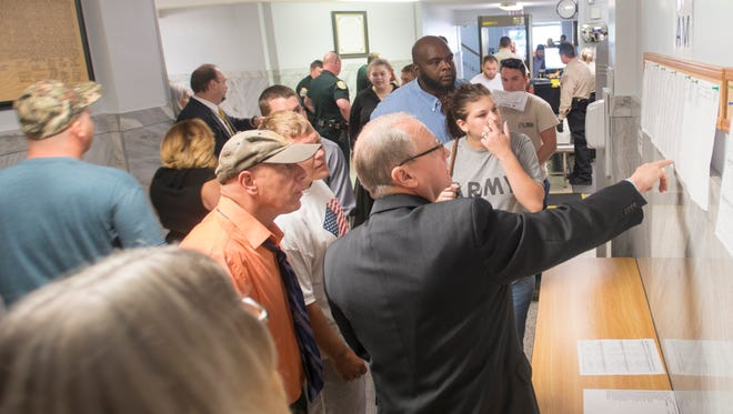 A crowd forms around the list of courtroom assignments at the Santa Rosa County Courthouse in Milton on Tuesday, May 30, 2017.  The courthouse was more crowded than usual due to a clerical error that more than doubled the court's daily dockets.