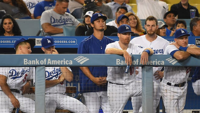 The Los Angeles Dodgers watch the game from the dugout in the ninth inning against the Arizona Diamondbacks at Dodger Stadium on September 6, 2017 in Los Angeles, California.