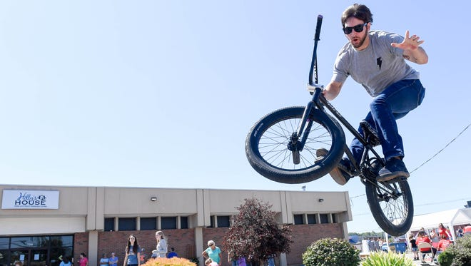Michael Barrow with Dans Comp does bike tricks on his BMX bike at the Holly House Fun Fair Sunday. The event featured carnival games, inflatables, food, haircuts and cruse-in, September 10, 2017.