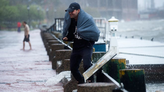 James Rmih reacts after water splashes on his back as water from the Savannah River begins to flow towards River Street due to high tide and Tropical Storm Irma rains on Monday, Sept. 11, 2017.