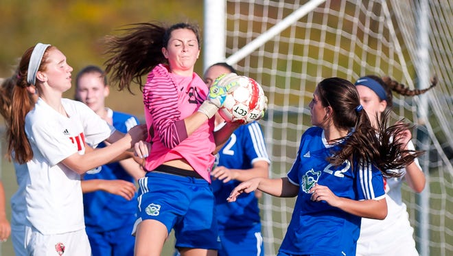 Colchester's Gabby Gosselin, center, snares a corner kick against Champlain Valley during Wednesday's girls soccer game in Hinesburg.
