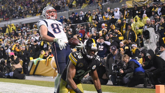New England Patriots tight end Rob Gronkowski (87) celebrates a two point conversion in the fourth quarter as Pittsburgh Steelers safety Sean Davis (28) looks away at Heinz Field.