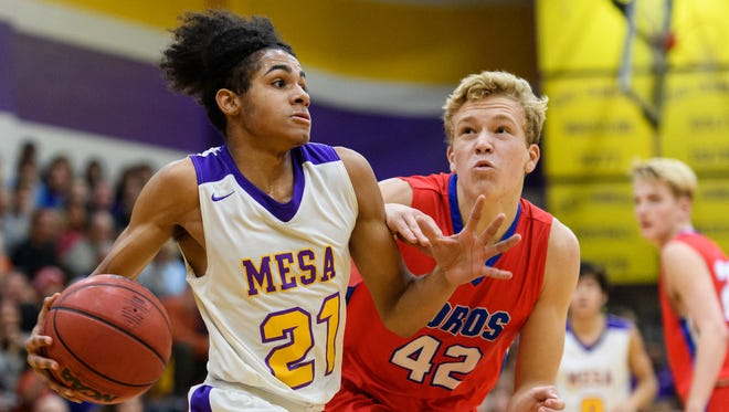 Mesa's Xavier Fuller (C) (21) drives the baseline with pressure from Mountain View's Preston Jones (42) in the second quarter of their game on Friday, Jan. 12, 2018, at Mesa High School in Mesa, Ariz.