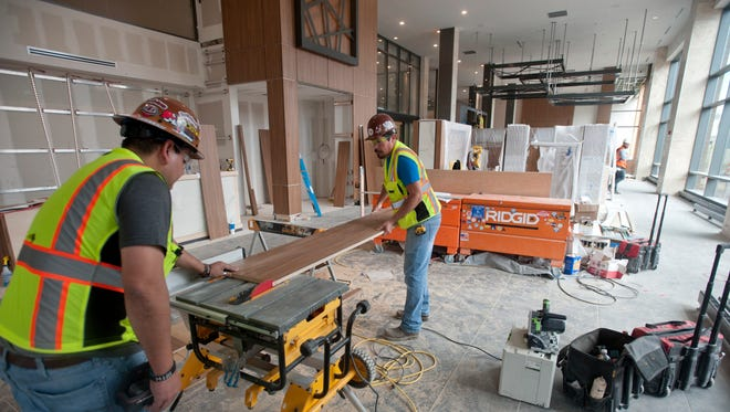 Construction workers cut down a wood plank in the lobby of the new AC Hotel Louisville Downtown on Tuesday, April 3, 2018. The hotel is set to open on April 30.