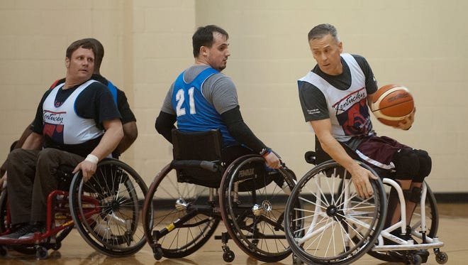 Jimmy Green of Mt. Washington tries to keep the ball away from Genc Hyseni, center, of Douglas Parkway, as the Louisville Spokes and Spires wheelchair basketball team mates scrimmage at Louisville Metro Parks'  Berrytown Recreational Center in Louisville. At left is Micah Jackson of Lexington who commutes to Louisville to play with the team.