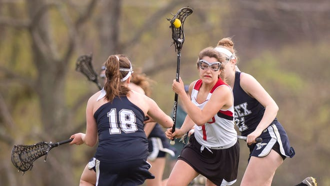 Champlain Valley's Lydia Maitland, center, charges up the field against Essex during a girls lacrosse game in Hnesburg on Friday, May 4, 2018.