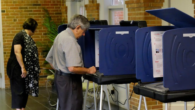 Voters cast their ballot at the Easlan Baptist church in Greenville. County turnout was light, election officials said.