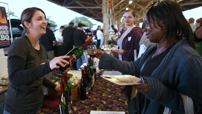 Brittany Morris of Fulkerson Winery, left, pours wine for Darlene Atkins of Rochester during the 2012 Festival of Food at the Public Market.