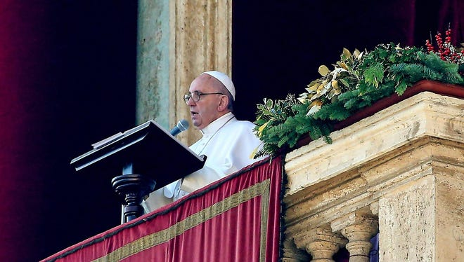 Pope Francis speaks to faithful during the traditional Urbi et Orbi (to the city and to the world) Christmas Day message and blessing  from the central balcony of St. Peters Basilica in Vatican City on Friday.