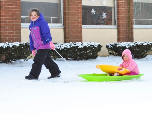 Mckenna and Kyleigh Mcglyn sledding in Ramsey on Sunday.