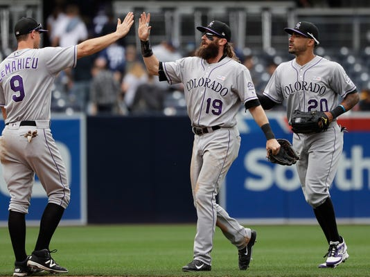 Colorado Rockies center fielder Charlie Blackmon (19) celebrates with second baseman DJ LeMahieu (9) and left fielder Ian Desmond after defeating the San Diego Padres in a baseball game Sunday, June 4, 2017, in San Diego. (AP Photo/Gregory Bull)