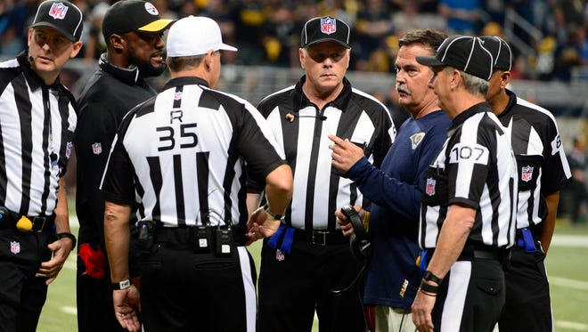 Pittsburgh Steelers head coach Mike Tomlin and St. Louis Rams head coach Jeff Fisher talk with officials after a small fire started during pregame introductions burning a section of the field before a game between the Pittsburgh Steelers and the St. Louis Rams at the Edward Jones Dome.