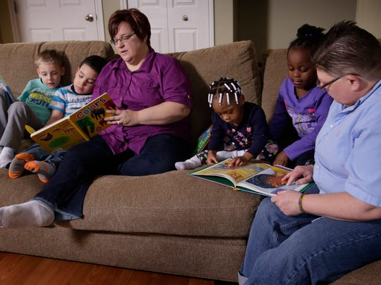 Jacob DeBoer-Rowse, 5, sits with his brother Nolan DeBoer-Rowse, 6, as April DeBoer, 44, reads with Rylee DeBoer-Rowse, 2, Ryanne DeBoer-Rowse, 5, with partner Jayne Rowse, 50, Thursday Jan. 29, 2015 at their Hazel Park home.